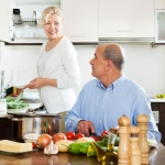 Mature man chopping vegetable and looking at his wife